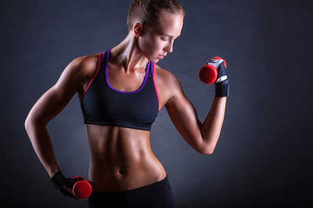 A young woman playing sports with weights on a dark background Reklamní fotografie
