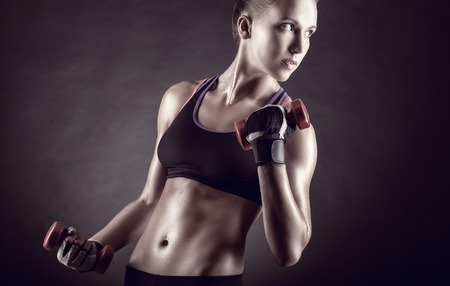 fitness abs female: Fitness girl with dumbbells on a dark background