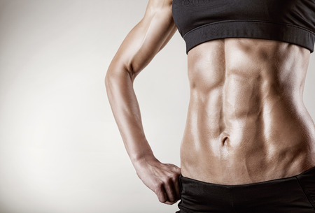 muscle woman: Close-up of the abdominal muscles young athlete on gray background