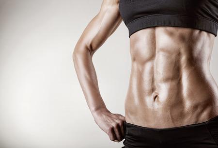 muscle: Primer plano de los m�sculos abdominales atleta joven sobre fondo gris