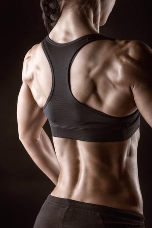 Atletische jonge vrouw toont spieren van de rug en de handen op een zwarte achtergrond