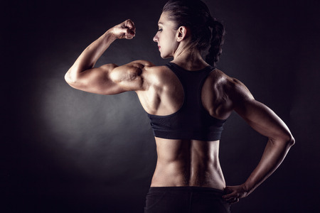 Athletic young woman showing muscles of the back and hands on a black background 스톡 콘텐츠