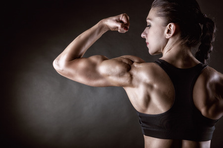 bicep: Athletic young woman showing muscles of the back and hands on a black background Stock Photo