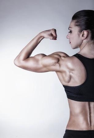 Atletische jonge vrouw toont spieren van de rug en handson op een grijze achtergrond Stockfoto