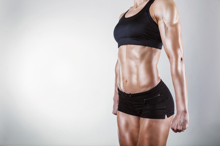 The body of a young athletic girl on gray background