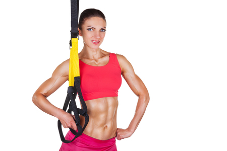 Beautiful athletic woman with functional loops for training isolated on white background photo