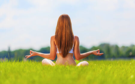 Young woman sitting in lotus position on nature