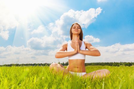 Young woman sitting in lotus position on nature photo