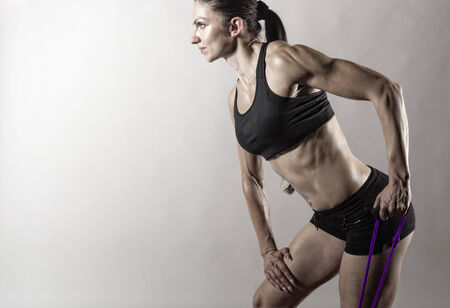 stretchy: Sportswoman exercising with a resistance band on grey  background