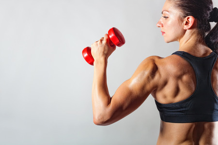 strong women: Fitness woman with barbells on grey background Stock Photo