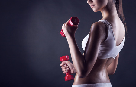 Fitness girl with dumbbells on a dark background. Back view Foto de archivo