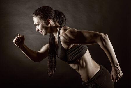 atleta corriendo: Mujer que se ejecuta sobre un fondo oscuro. Vista lateral