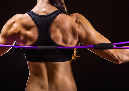elastic: Close-up of athletes performing back exercises with a resistance group against a dark background Stock Photo