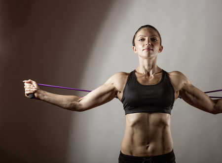 woman rope: Sportswoman exercising with a resistance band on grey  background
