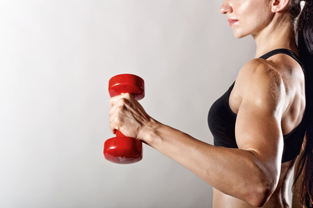muscle girl: Fitness woman with barbells on grey background Stock Photo