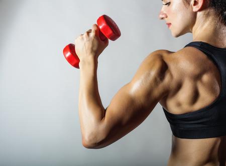 Fitness femme avec haltères sur fond gris