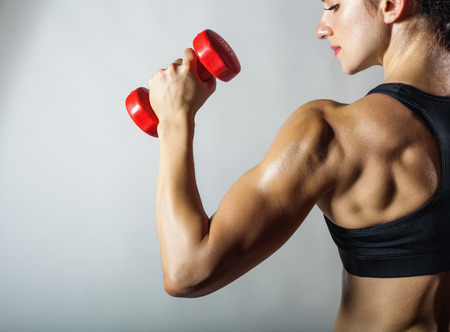 Fitness woman with barbells on grey background Stock Photo