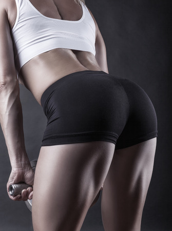 squat: Woman doing exercises with dumbbell squats on a dark background