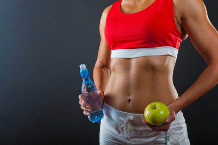 Torso of a woman with a bottle of water and green apple on a dark background Stock Photo