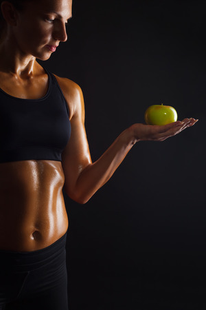 Muscular woman with apple on dark background