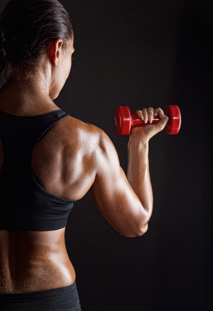 athletic body: Fitness woman with barbells on dark background
