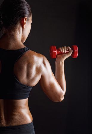 cuerpo femenino: Mujer de la aptitud con pesas sobre fondo oscuro Foto de archivo