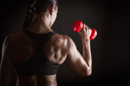 Fitness woman with barbells on dark background