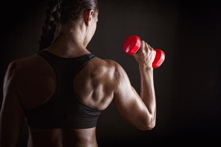 gimnasio mujeres: Mujer de la aptitud con pesas sobre fondo oscuro Foto de archivo