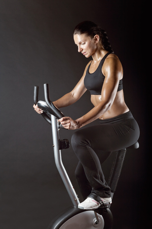 Athletic woman exercising workout on a stationary bike