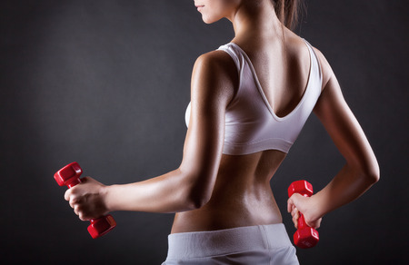 fitness abs female: Fitness woman with dumbbells on a dark background. Back view
