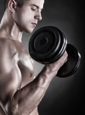 powerfully: Young muscular man with dumbbells on black background Stock Photo
