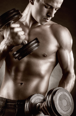 male bodybuilder: Young muscular man with dumbbells on black background Stock Photo