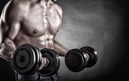 body torso: Closeup of a muscular young man lifting weights on dark background Stock Photo