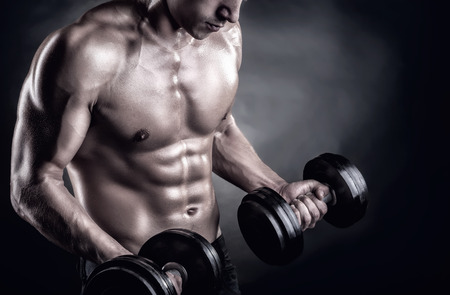 Closeup of a muscular young man lifting weights on dark background Stockfoto