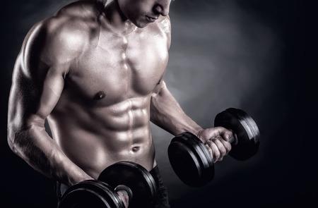 abdominal fitness: Primer plano de un joven muscular pesos de elevación del hombre sobre fondo oscuro