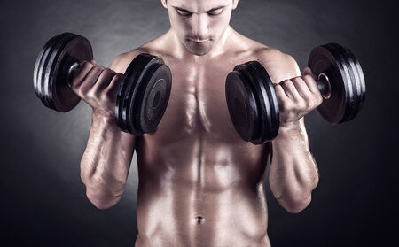 lifting: Closeup of a muscular young man lifting weights on dark background Stock Photo