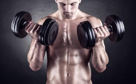 levantando pesas: Primer plano de un joven muscular pesos de elevaci�n del hombre sobre fondo oscuro