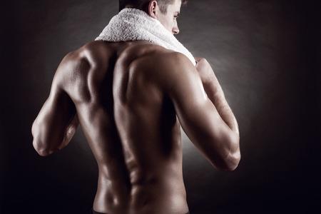 uomo nudo: Giovane uomo dopo la formazione su sfondo scuro Archivio Fotografico