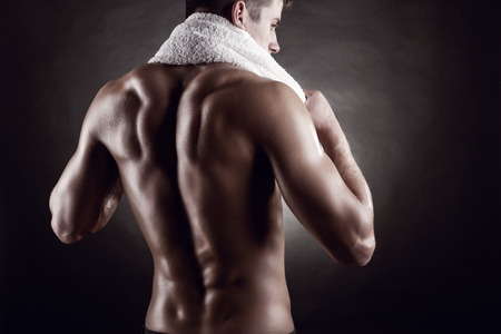 hombre desnudo: Hombre joven después del entrenamiento en el fondo oscuro Foto de archivo