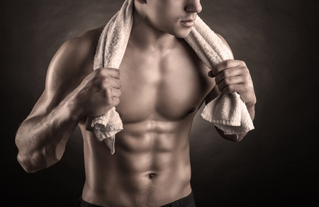 naked abs: Healthy muscular young man after a workout on dark background Stock Photo