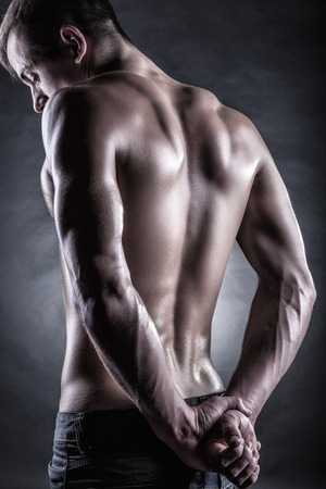 nude back: Strong athletic man back on dark background
