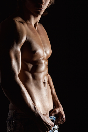 nude sport: Muscular male torso on black background Stock Photo
