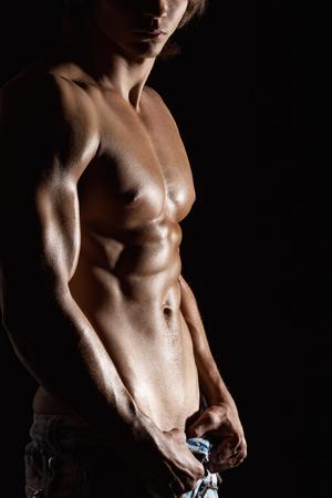 desnudo masculino: Muscular torso masculino sobre fondo negro Foto de archivo