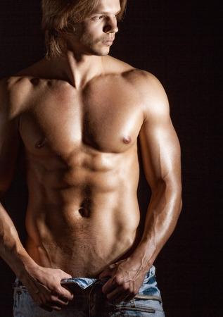 nackt: Sexy junger Mann auf einem dunklen Hintergrund