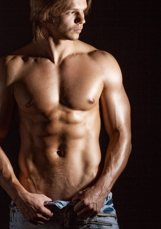 nude abs: Sexy young man on a dark background