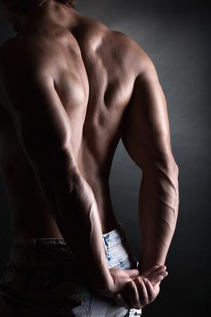 nudo maschile: Forte uomo atletico torna su sfondo scuro