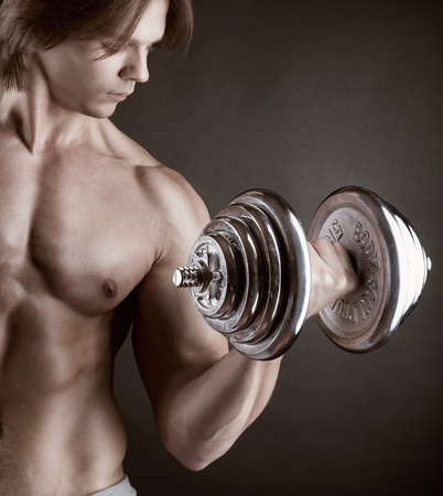 powerfully: Fit muscular man exercising with dumbbell on dark background Stock Photo