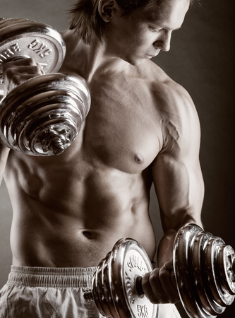 Young muscular man with dumbbells on black background photo