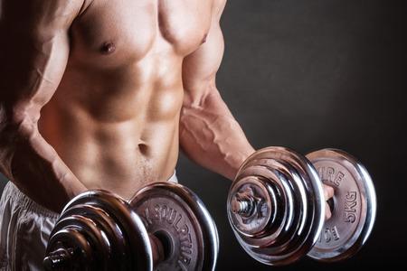 levantando pesas: Primer plano de un joven muscular pesos de elevación del hombre sobre fondo oscuro