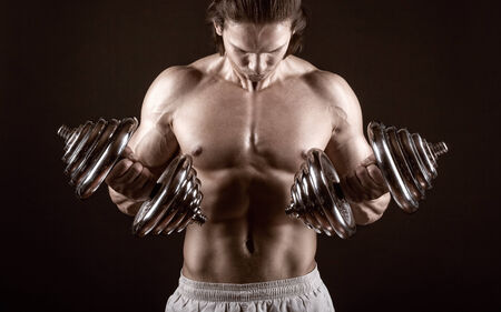 heavy weight: Muscular man with dumbbells on black background Stock Photo